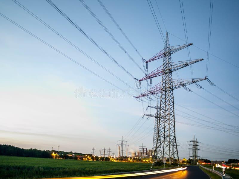 Опоры электричества на заходе солнца транспортируя экологически чистую энергию стоковая фотография rf