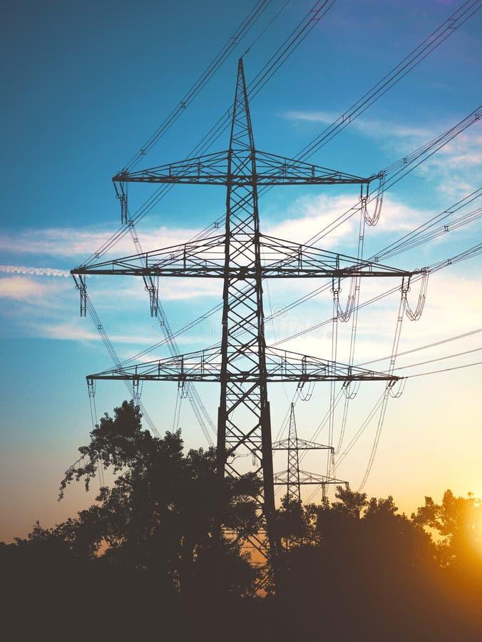 Опоры электричества на заходе солнца транспортируя экологически чистую энергию стоковое изображение