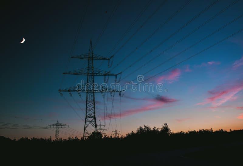 Опоры электричества на заходе солнца транспортируя экологически чистую энергию стоковые фотографии rf
