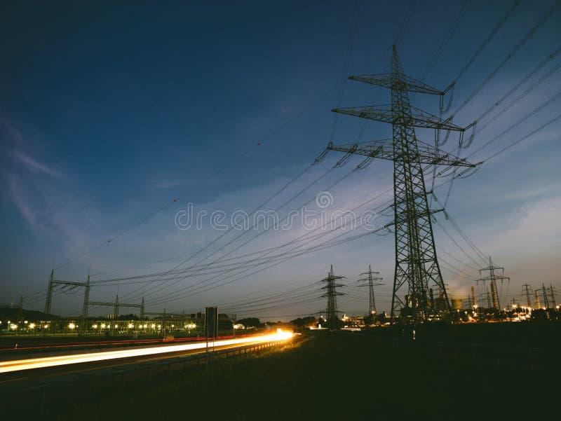 Опоры электричества на заходе солнца транспортируя экологически чистую энергию стоковые изображения