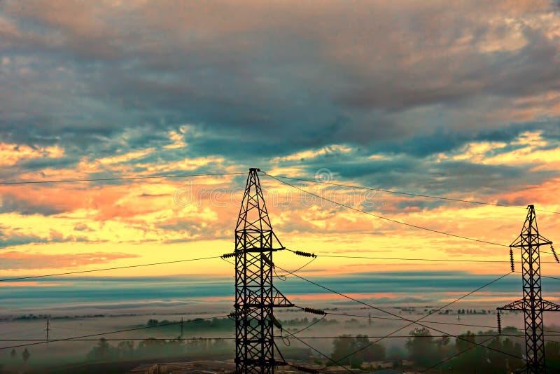 2 опоры электричества против драматического неба захода солнца стоковая фотография