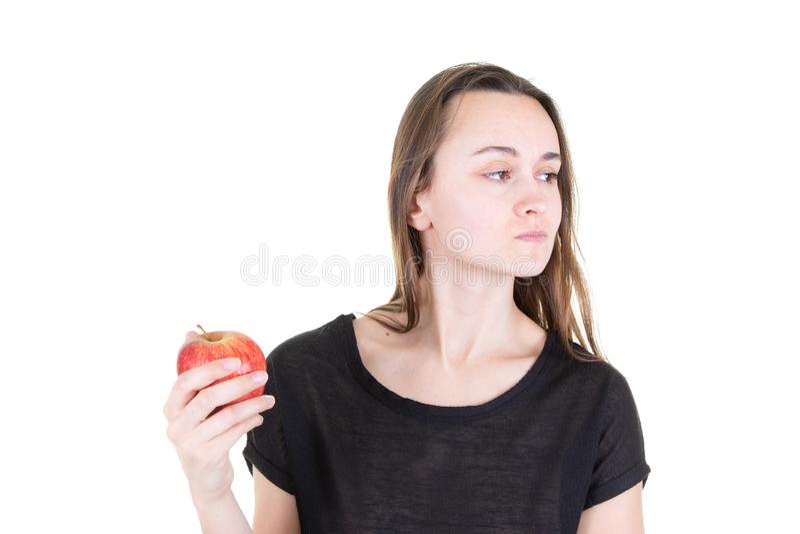 Опостылетая молодая женщина держа красное яблоко и смотря в сторону в здоровом питании начала вегетарианском стоковые фотографии rf