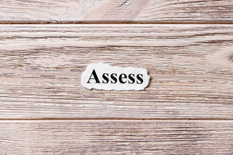 ОПРЕДЕЛИТЕ слова на бумаге Концепция Слова ASSESS на деревянной предпосылке стоковое фото rf