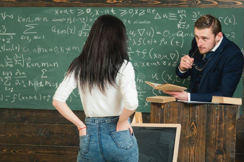 Определять студента уча исходы Учитель слушает к студенту девушки в классе Женщина вида сзади в джинсах отвечает для того чтобы у стоковые фотографии rf