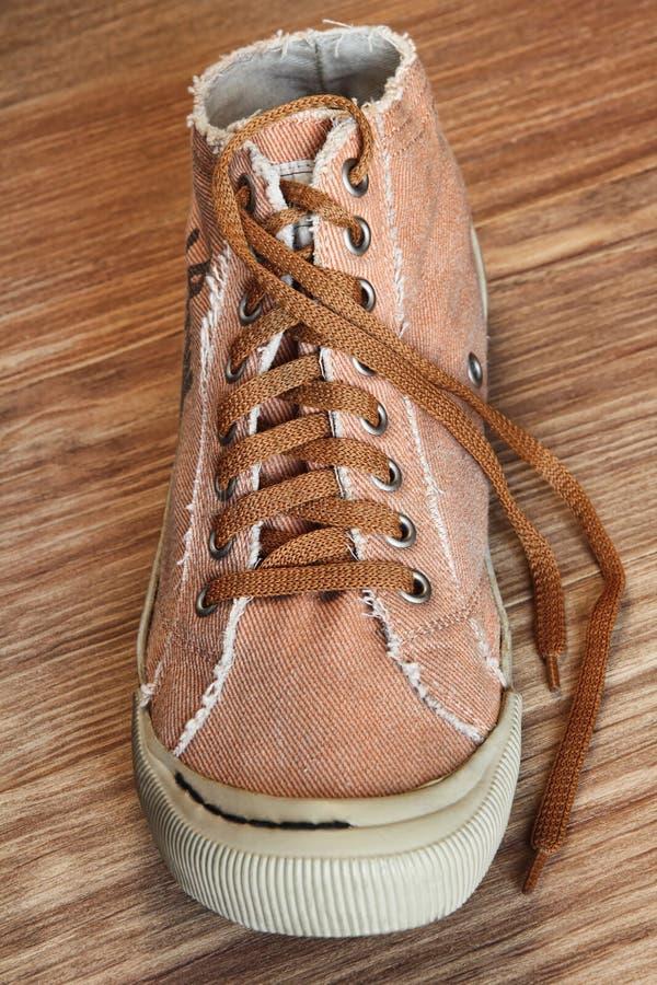 Определите ультрамодный ботинок спортзала на деревянной крупном плане принятом предпосылкой стоковые изображения rf