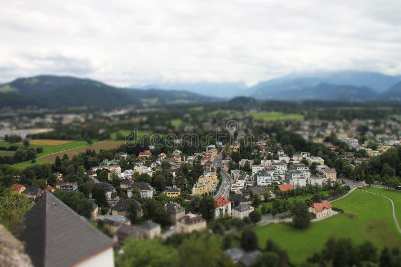 Опрокиньте и перенесите взгляд зданий Зальцбурга среди гор стоковое изображение