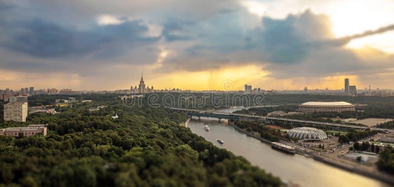 Опрокиньте и перенесите взгляд ненастной зоны холмов Ленина с отражениями реки, шлюпками, стадионом спорта и профилем университет стоковое фото