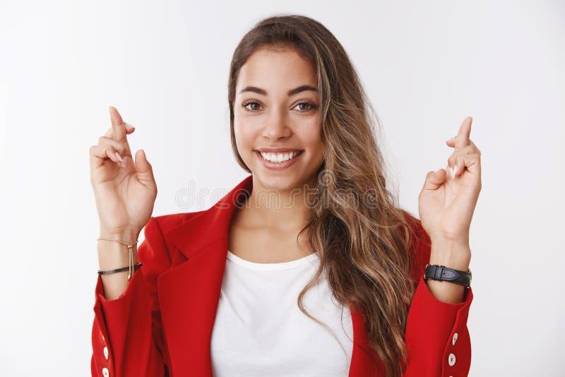 Оптимистическая счастливая женщина делая успех желания усмехаясь направленный, перекрестные пальцы удачи grinning смотрящ подающи стоковое изображение rf