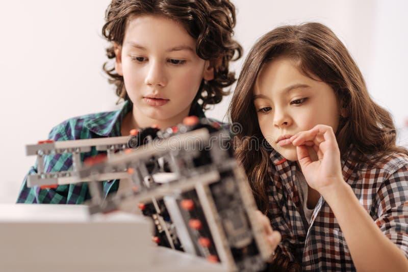 Оптимистический робот программирования детей в студии науки стоковое фото
