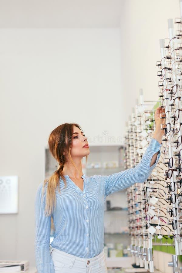 оптически магазин Женщина около витрины ища Eyeglasses стоковые изображения