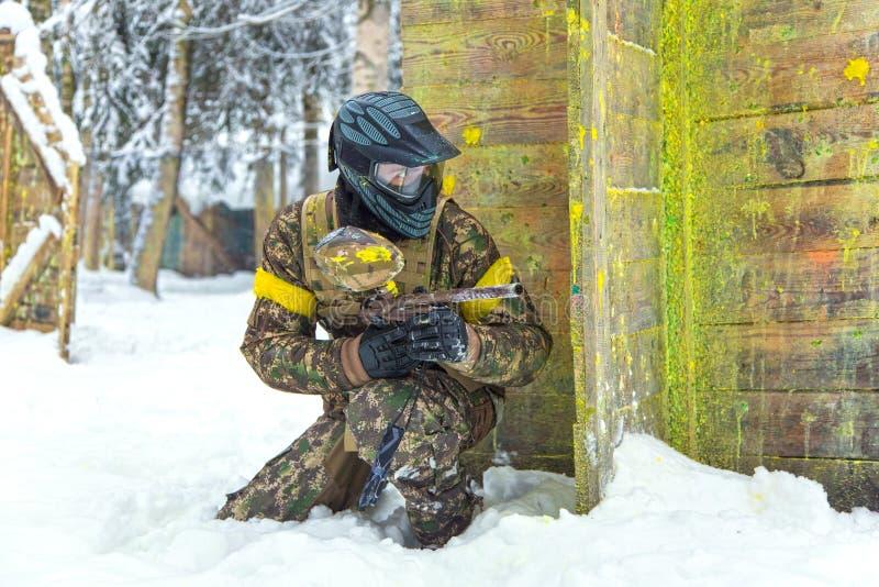 Опытный спортсмен в профессиональном панцыре пейнтбола на зиме стоковое фото