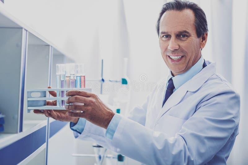 Опытный химик кладя пробирки в заказ стоковые фотографии rf