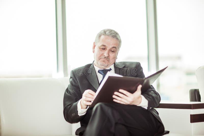 Опытный юрист рассматривает документы с терминами нового контракта стоковые фотографии rf