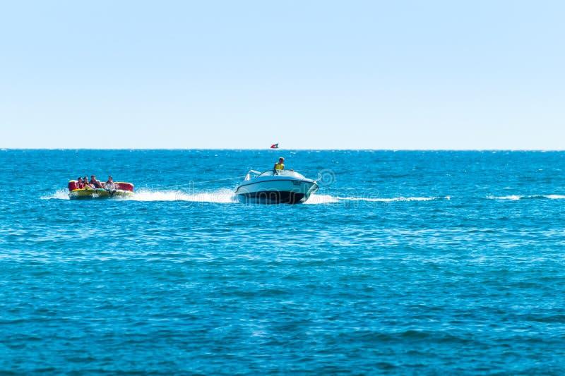 Опыт езды донута водных видов спорта шлюпки скорости, люди в раздувном донуте вытянул побережьями Albufeira, Алгарве Португалии стоковая фотография rf