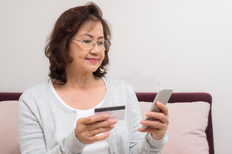 Оплата счастливой азиатской старшей женщины ходя по магазинам онлайн с кредитной карточкой стоковое фото