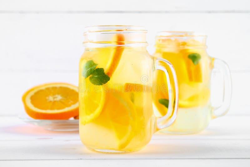 Оранжевая вода вытрезвителя в опарниках каменщика на белом деревянном столе Здоровая еда, пить стоковая фотография