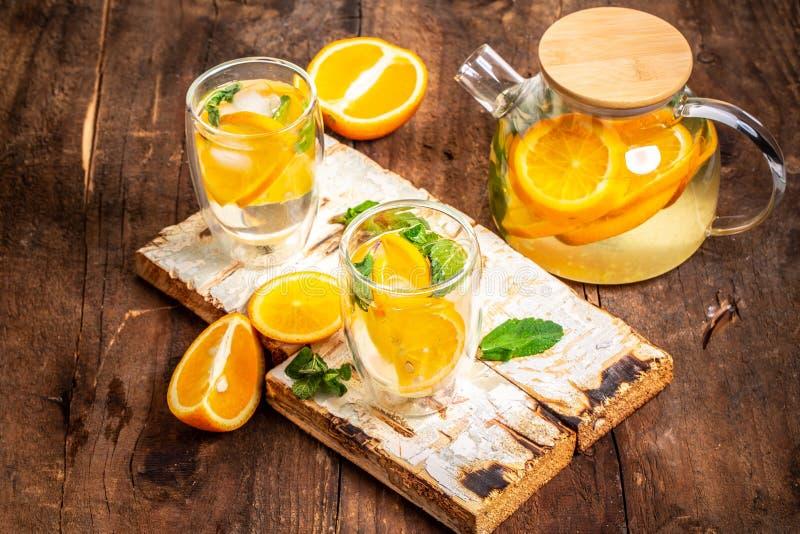 Оранжевая вода вытрезвителя в опарниках каменщика на деревянном столе Здоровая еда, напитки, фитнес, здоровая концепция диеты пит стоковая фотография rf