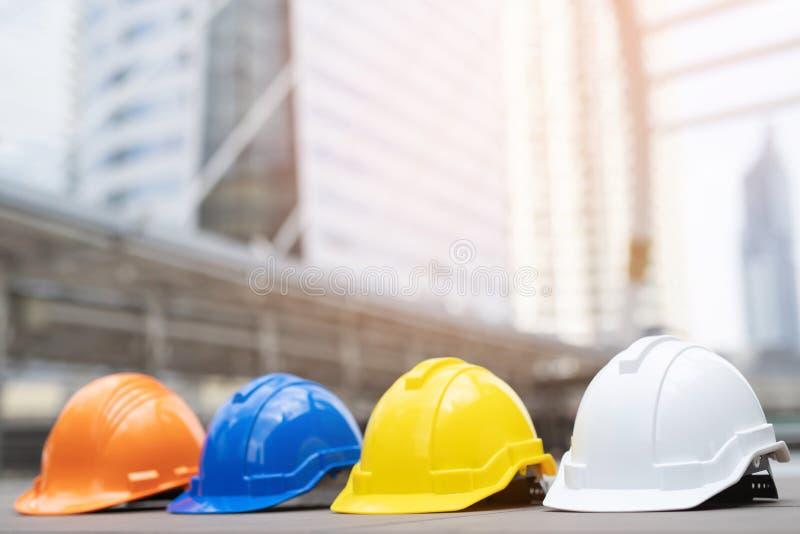 Оранжевая, желтая, голубая, белая трудная шляпа шлема носки безопасности в проекте на конструкции стоковая фотография rf
