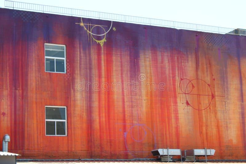 Оранжевая и фиолетовая настенная роспись в районе искусства в Лос двигает под углом стоковое изображение