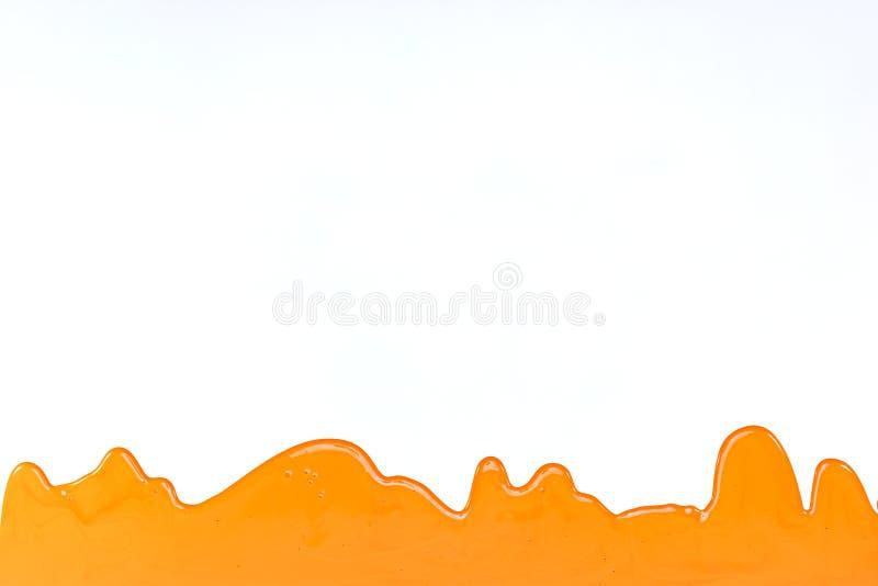 Оранжевая краска лить на белой предпосылке Концепция реновации стоковое фото