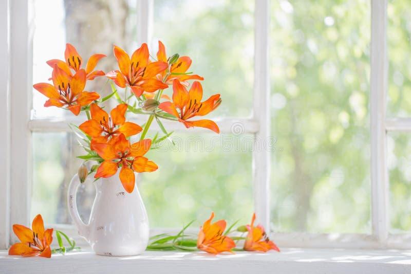 Оранжевая лилия на windowsill стоковая фотография