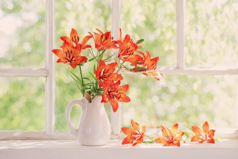 Оранжевая лилия на windowsill стоковая фотография rf