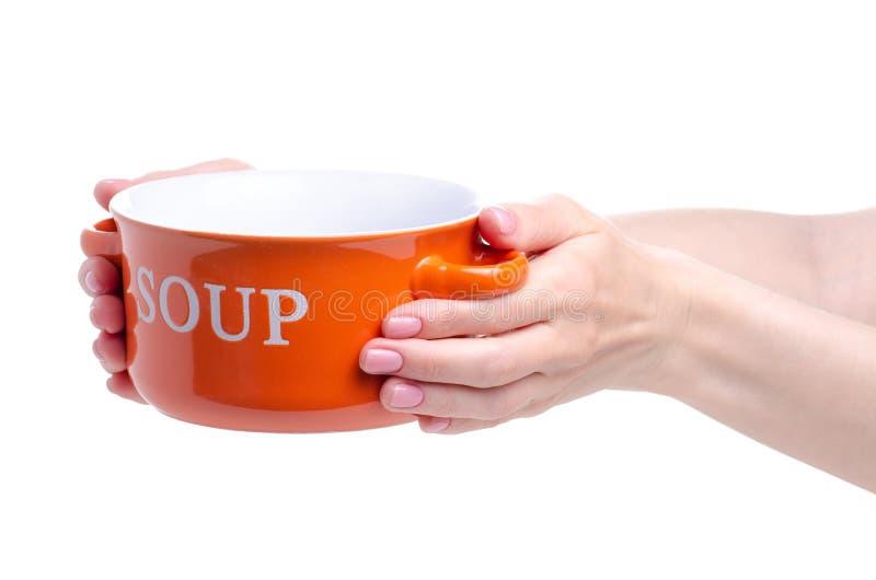 Оранжевая плита для супа в руке стоковые фотографии rf