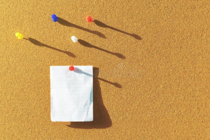 Оранжевая пробковая доска с одним примечанием бумаги приколола и несколько штырей другого цвета выше с тенями от бортового солнеч стоковая фотография rf