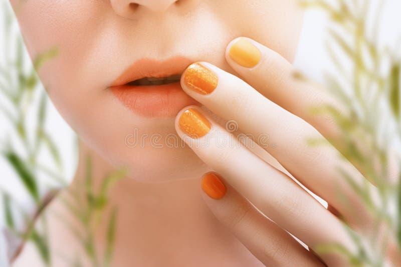 Оранжевое искусство ногтя и женский крупный план стороны стоковые изображения