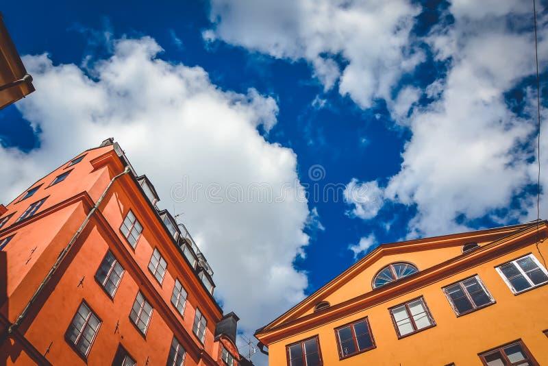 Оранжевое и красное здание с много окон в городе Стокгольма, Швеции на солнечный летний день против предпосылки пасмурное стоковая фотография