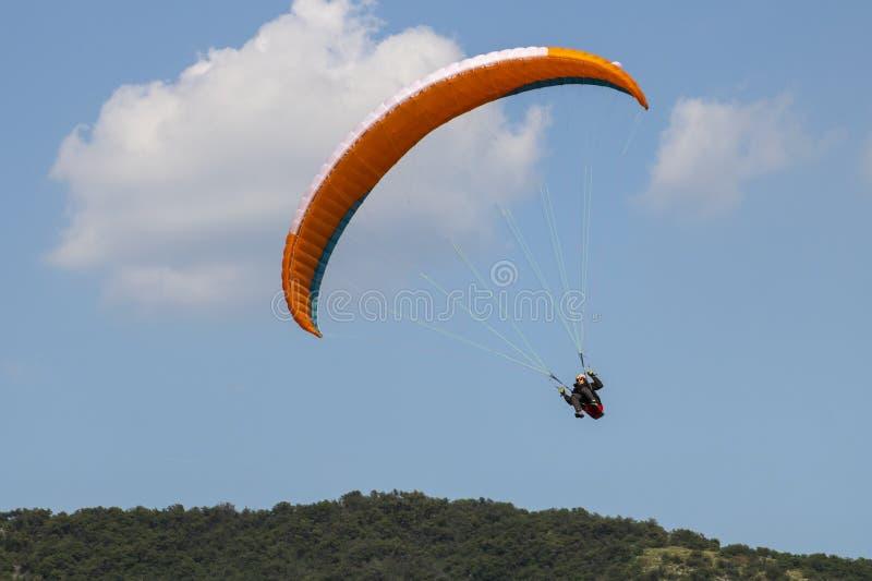 Оранжевое летание параплана между небом и землей стоковые изображения