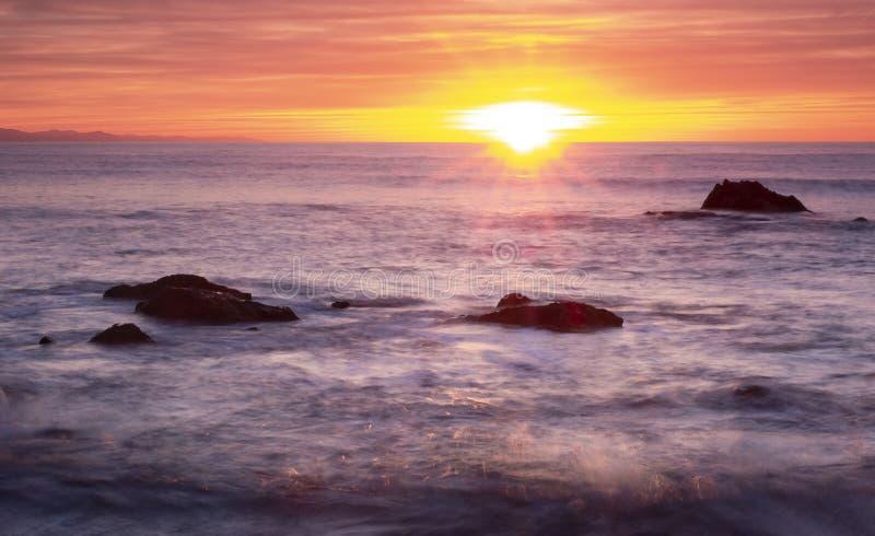 Оранжевое небо на заходе солнца, солнечном свете отражает на воде стоковые фото