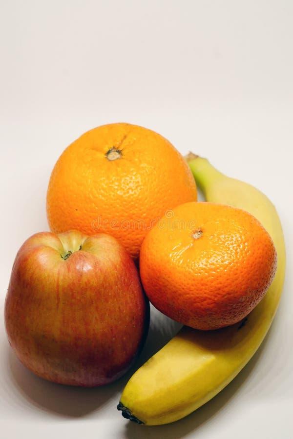 Оранжевые банан и яблоко мандарина на белой изолированной предпосылке стоковое изображение rf