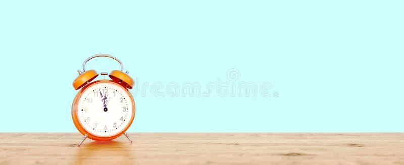 Оранжевые винтажные часы на предпосылке teal показывая почти 12, последняя мельчайшая концепция стоковое фото