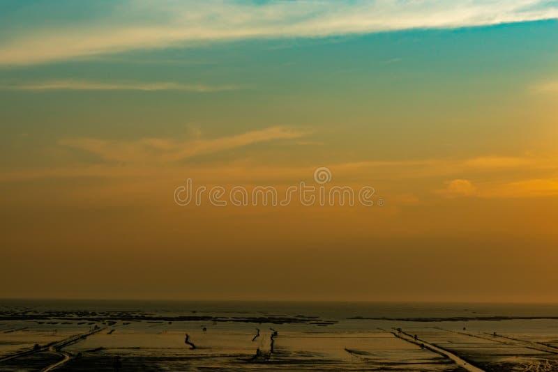 Оранжевые и голубые небо и облака захода солнца Заход солнца на пляже Пляж грязи на seashore Красивый горизонт на сумраке Ландшаф стоковые изображения rf
