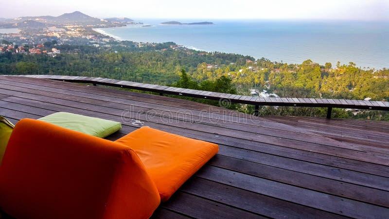 Оранжевые и зеленые расслабляющие валики с видом на море стоковая фотография