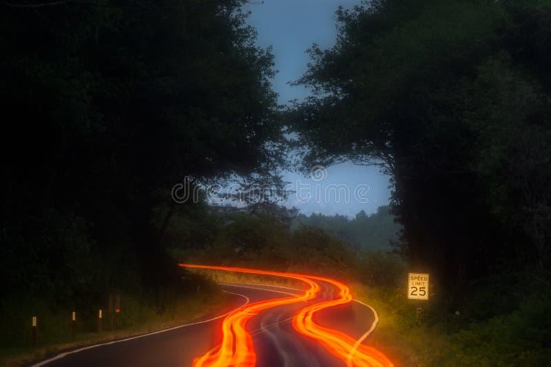 Оранжевые, красные и желтые следы света автомобиля вдоль кривой дороги в горах вечером со знаком ограничения в скорости Транспорт стоковое изображение