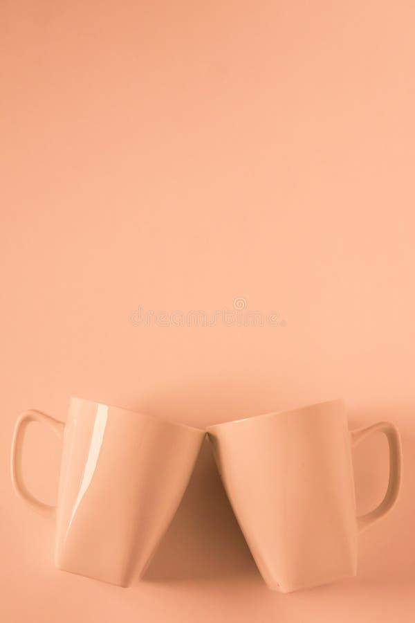 Оранжевые кружки кофе на оранжевой предпосылке clinking в приветственных восклицаниях с пустым copyspace стоковые изображения rf