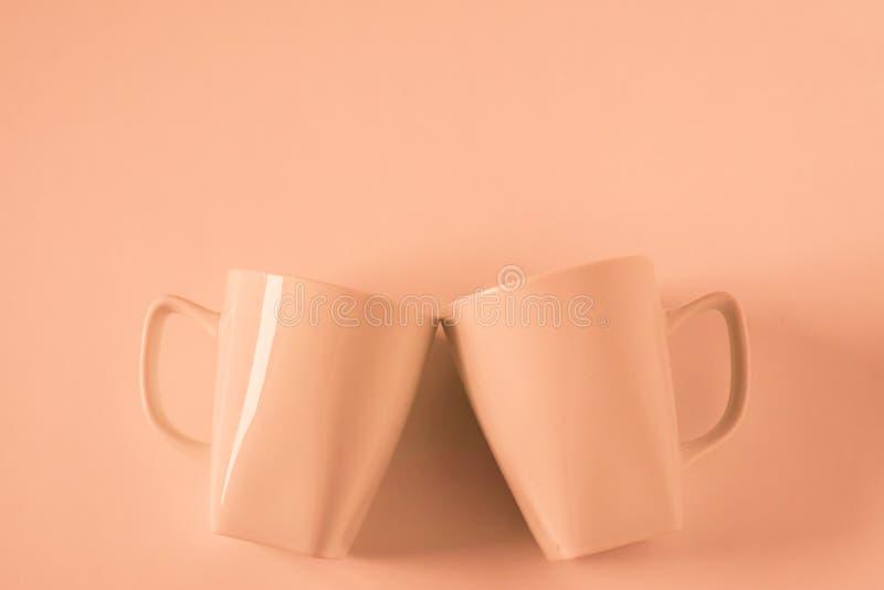 Оранжевые кружки кофе на оранжевой предпосылке clinking в приветственных восклицаниях с пустым copyspace стоковое фото rf