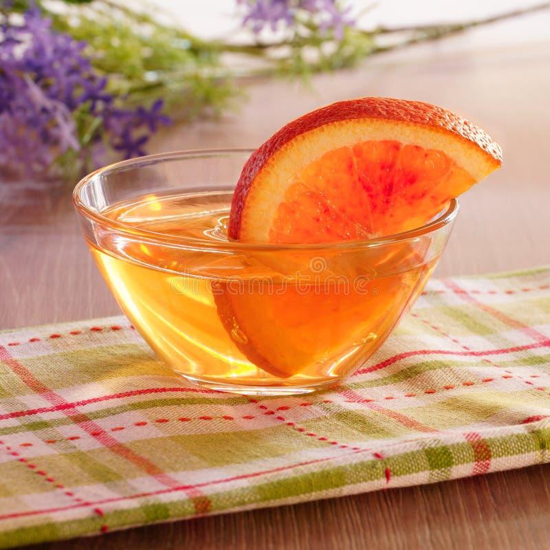 Оранжевые куски студня и апельсина в стеклянной чашке стоковое фото