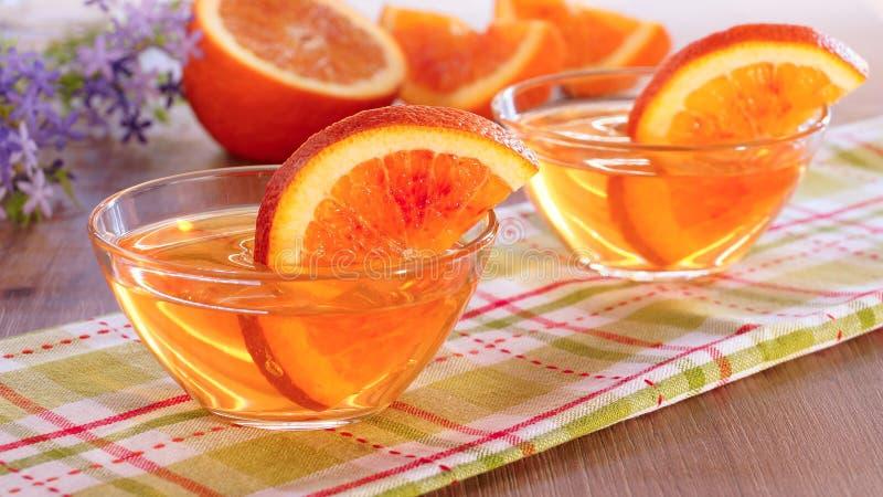Оранжевые куски студня и апельсина в стеклянной чашке стоковое изображение