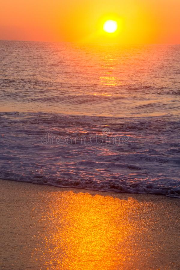 Оранжевые небо и волны восхода солнца стоковые изображения