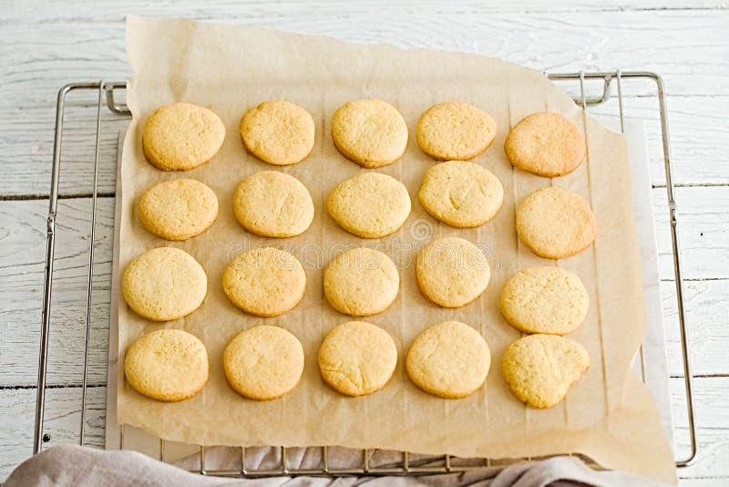 Оранжевые печенья масла на бумаге выпечки и коммуникационном проводе стоковые фото