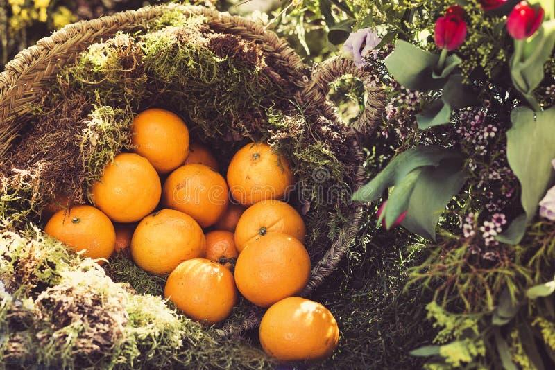Оранжевые плоды в плетеной корзине в рынке стоковые изображения