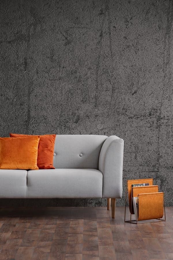 Оранжевые подушки на сером кресле в темном интерьере просторной квартиры с бетонной стеной и деревянным полом Реальное фото стоковые изображения
