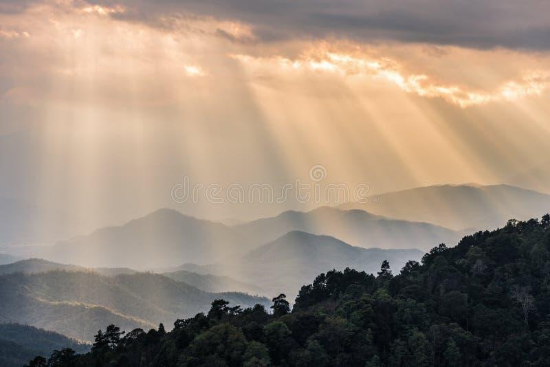 Оранжевые солнечные лучи светя через облачное небо к горной цепи стоковые фотографии rf