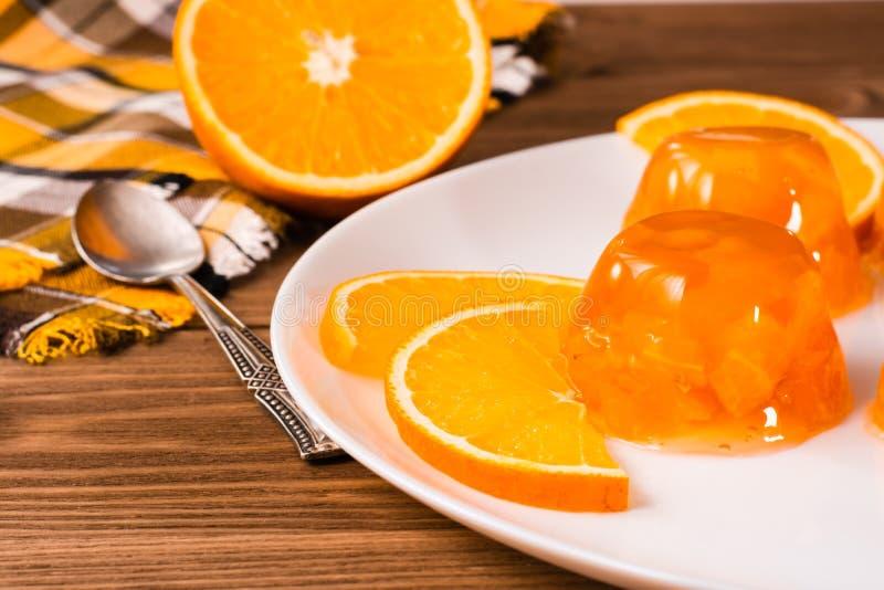 Оранжевые студень и апельсины на плите стоковое фото rf