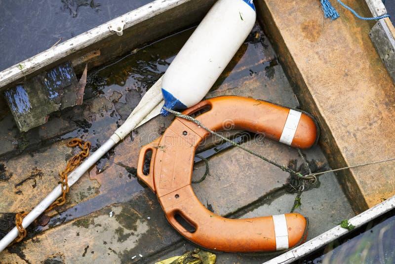 Оранжевые томбуй и весло безопасности воды на деревянной шлюпке стоковое фото