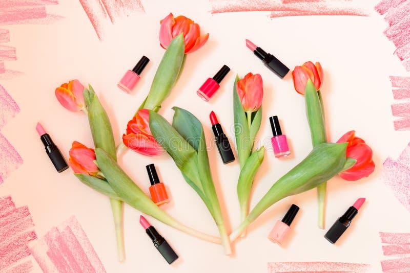 Оранжевые тюльпаны, красочные губные помады и маникюры на пастельной предпосылке стоковое изображение