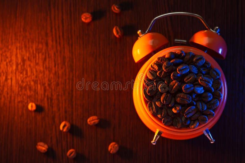 Оранжевый будильник с кофейными зернами на деревянном столе стоковое фото